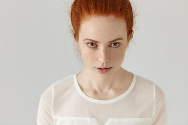 Bovenaanzicht van mooie blanke vrouw met sproeten over haar hele gezicht poseren binnenshuis, staren, met sluwe verleidelijke blik. mensen en levensstijl