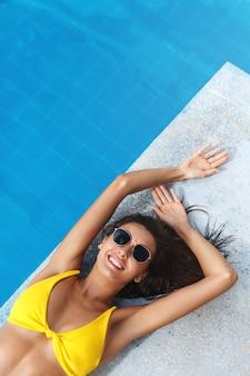Bovenaanzicht van mooie brunette vrouw met gouden zomer tan, liggend in de buurt van zwembad en glimlachend in zonnebril en bikini.