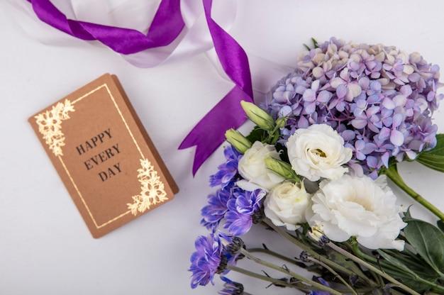 Bovenaanzicht van mooie en mooie bloemen zoals rozen madeliefjebloemen met kaart op een witte achtergrond