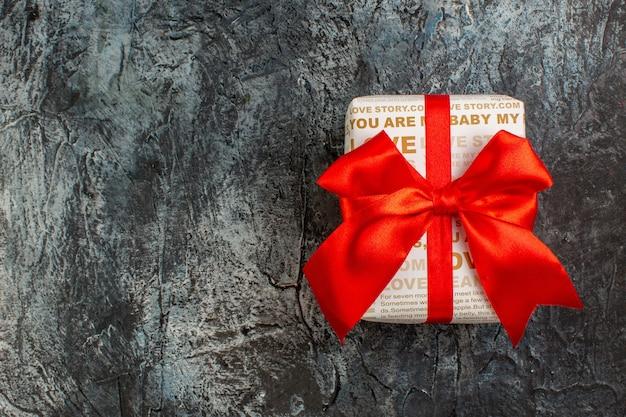 Bovenaanzicht van mooie geschenkdoos gebonden met rood lint aan de linkerkant op ijzige donkere achtergrond