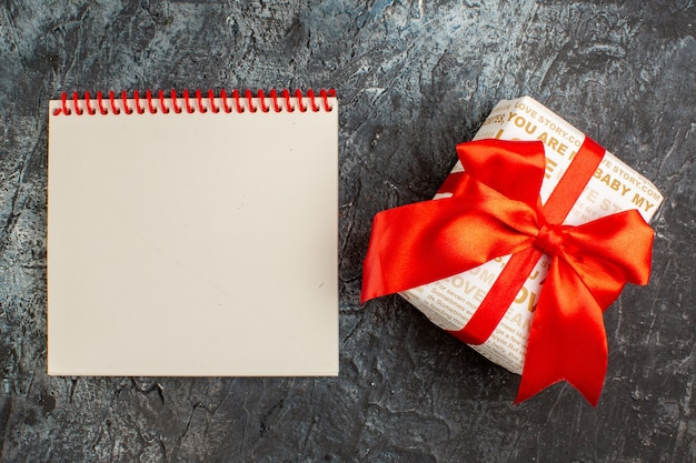 Bovenaanzicht van mooie geschenkdoos gebonden met rood lint en notitieboekje op ijzige donkere achtergrond