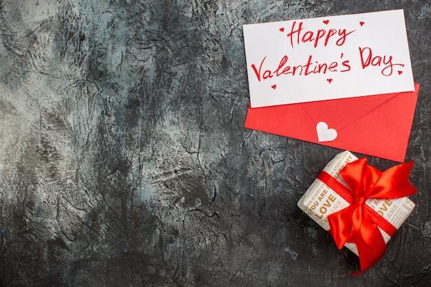 Bovenaanzicht van mooie geschenkdoos gebonden met rood lint voor valentijnsdag aan de linkerkant op ijzige donkere achtergrond