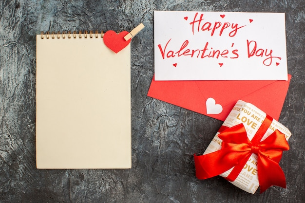 Bovenaanzicht van mooie geschenkdoos gebonden met rood lint voor valentijnsdag en notitieboekje op ijzige donkere achtergrond