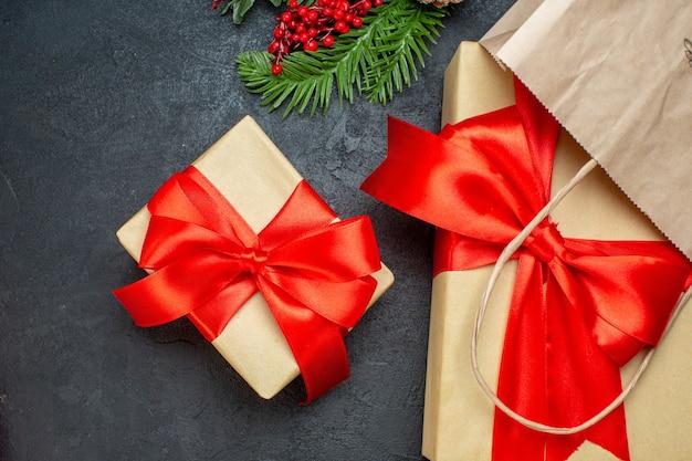 Bovenaanzicht van mooie geschenken met rood lint en dennentakken op donkere backgrround