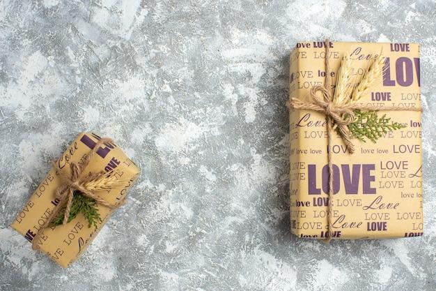 Bovenaanzicht van mooie grote en kleine kerstcadeaus met liefdesinscriptie op ijsoppervlak