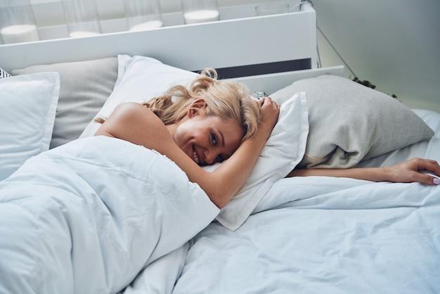 Bovenaanzicht van mooie jonge lachende vrouw die wakker wordt terwijl ze thuis in bed ligt
