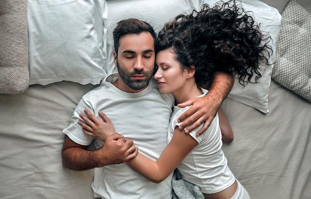 Bovenaanzicht van mooie jonge paar knuffelen tijdens het slapen samen in bed thuis