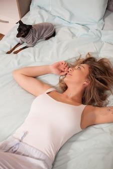 Bovenaanzicht van mooie jonge vrouw in pyjama en haar hondje ontspannen in bed 's nachts.