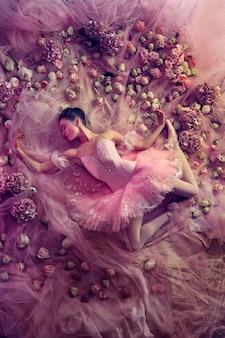 Bovenaanzicht van mooie jonge vrouw in roze ballet tutu omgeven door bloemen