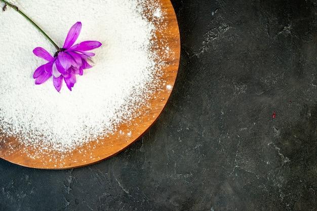 Bovenaanzicht van mooie paarse bloem op houten snijplank op zwarte achtergrond met vrije ruimte