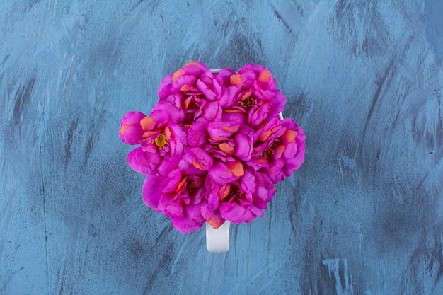 Bovenaanzicht van mooie paarse bloemen in een kopje op blauw.
