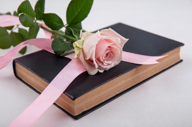 Bovenaanzicht van mooie roze roos met bladeren over een boek op een witte achtergrond