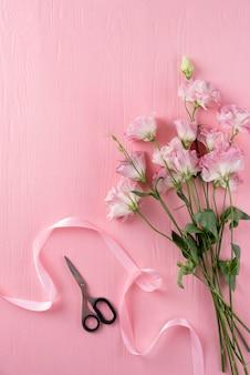Bovenaanzicht van mooie rozen met schaar en lint
