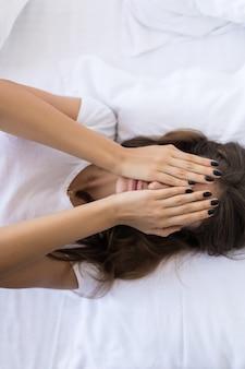 Bovenaanzicht van mooie sexy jonge vrouw die haar gezicht bedekt terwijl ze in bed ligt