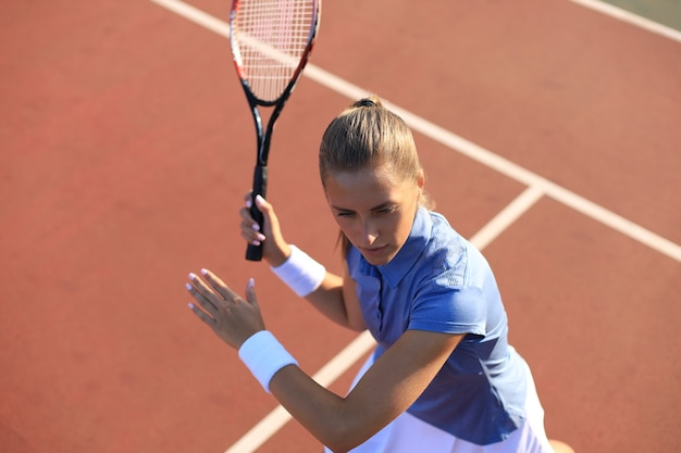 Bovenaanzicht van mooie tennisser klaar om de bal op de tennisbaan te dienen.