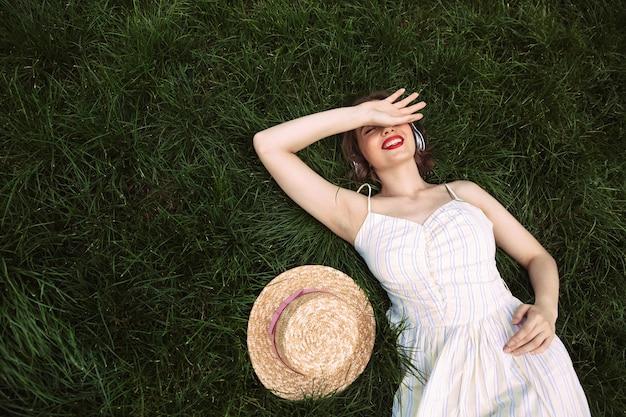 Bovenaanzicht van mooie vrouw in jurk en koptelefoon liggend op gras met gesloten ogen en muziek luisteren