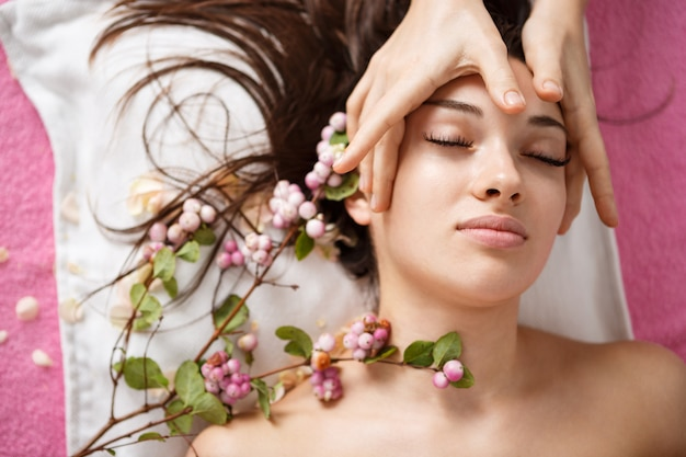 Bovenaanzicht van mooie vrouw in spa liggen met bloemen