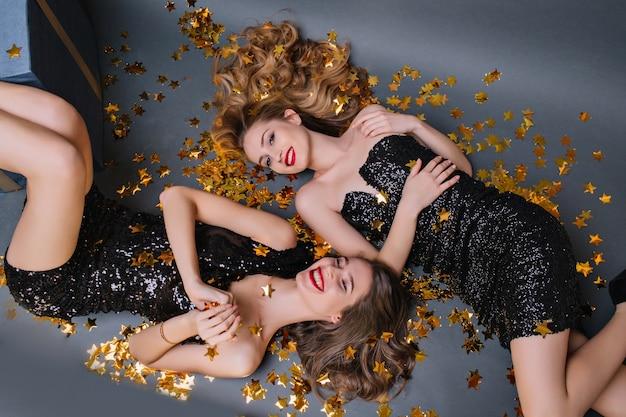 Bovenaanzicht van mooie vrouwen poseren op de vloer met sparkle confetti. foto van bovenaf van grappige meisjes die samen na nieuwjaarsfeest rusten.