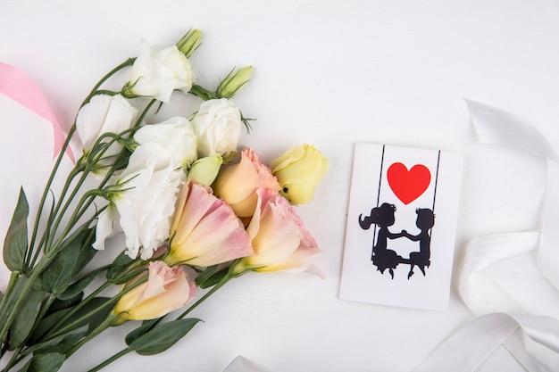 Bovenaanzicht van mooie witte rozen met liefde kaart op een witte achtergrond