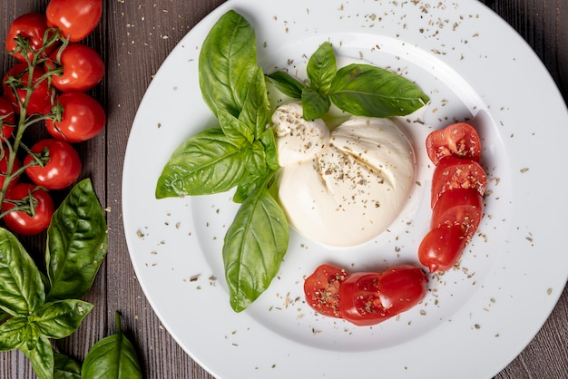 Bovenaanzicht van mozzarella en cherry tomaten op houten tafel