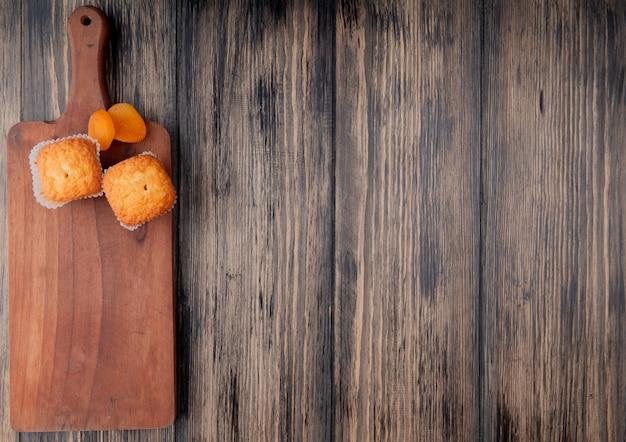 Bovenaanzicht van muffins en gedroogde abrikozen op houten snijplank op rustieke oppervlak met kopie ruimte