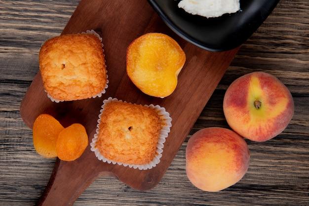 Bovenaanzicht van muffins met gedroogde abrikozen op houten snijplank en verse perziken op rustieke
