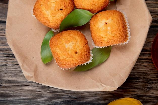 Bovenaanzicht van muffins op een ambachtelijke bruin papier op rustieke