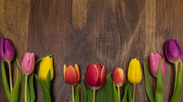Bovenaanzicht van multicolor voorjaar tulpen op de houten ondergrond