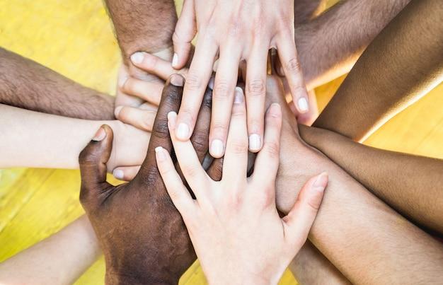 Bovenaanzicht van multiraciale stapelende handen - internationaal vriendschapsconcept met multi-etnische mensen