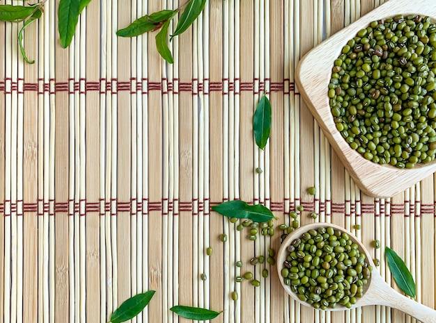 Bovenaanzicht van mung bean zaden op een houten lepel geplaatst op een japanse mat