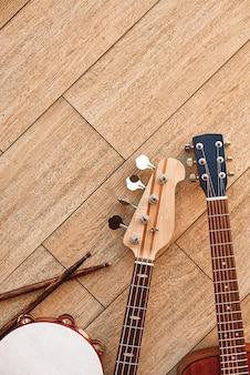 Bovenaanzicht van muziekinstrumenten: gitaren, drums met stokken liggend op lichte houten achtergrond. muziek studio. muziekinstrumenten.