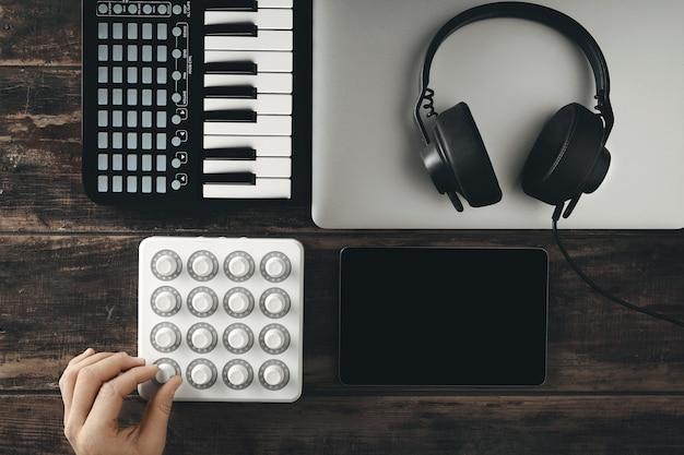 Bovenaanzicht van muziekproductie set midi mixer bediening, pianotoetsenbord, tablet, laptop en zwarte dj koptelefoon met lederen oorschelp