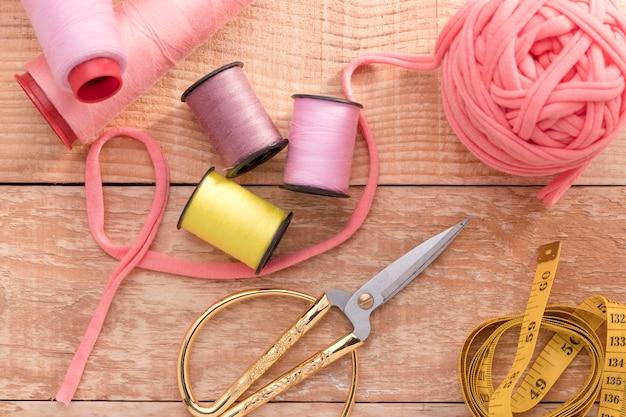 Bovenaanzicht van naaigaren met meetlint en schaar