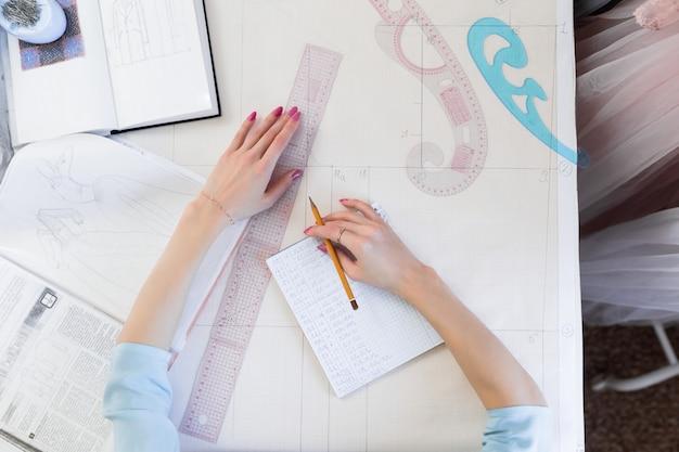 Bovenaanzicht van naaister handen maken een patroon op een wit calqueerpapier.