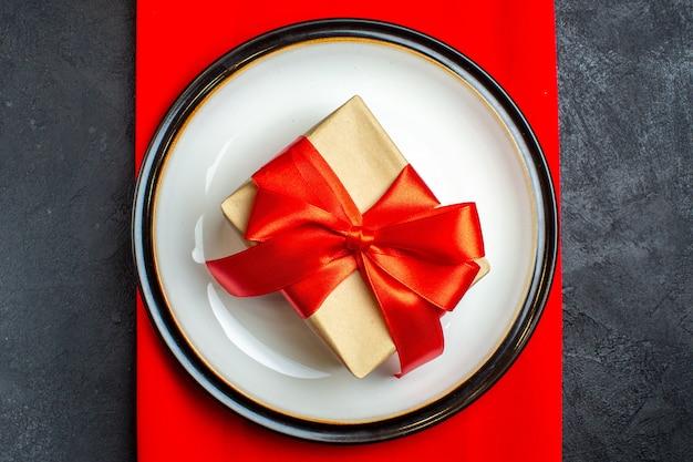 Bovenaanzicht van nationale kerstmaaltijd achtergrond met cadeau met boogvormig rood lint op lege borden op een rood servet op zwarte achtergrond
