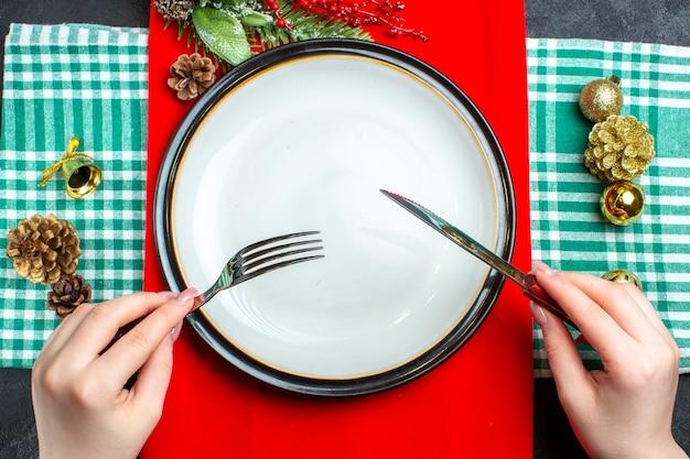 Bovenaanzicht van nationale kerstmaaltijd achtergrond met lege borden bestek set decoratie accessoires op groene gestripte handdoek