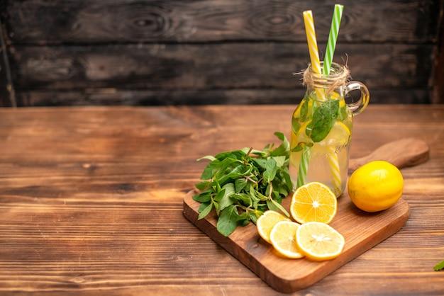 Bovenaanzicht van natuurlijk vers detoxwater geserveerd met buisjes munt en sinaasappel aan de linkerkant op een houten tafel