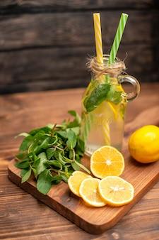 Bovenaanzicht van natuurlijk vers detoxwater geserveerd met buisjes munt en sinaasappel op een houten tafel