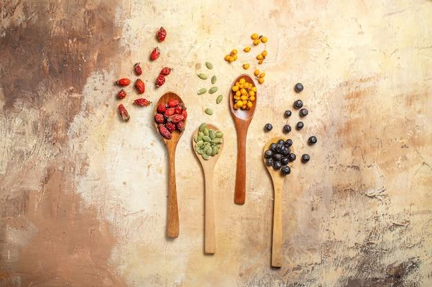 Bovenaanzicht van natuurlijke en verse verschillende soorten fruit in lepels