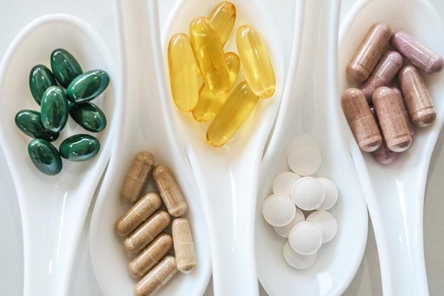 Bovenaanzicht van natuurlijke vitamine supplement op witte lepel als frame van marmeren textuur muur. gezond eten levensstijl trend concept.