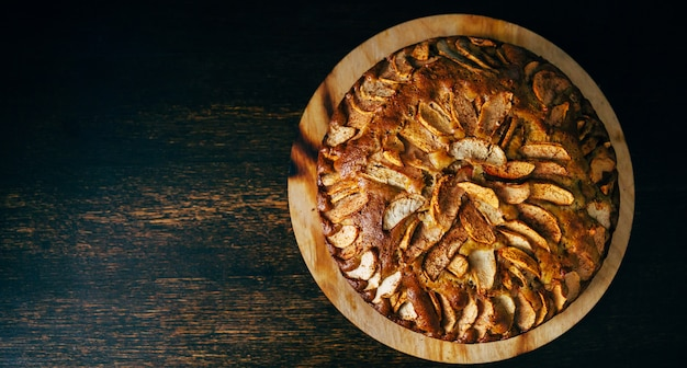 Bovenaanzicht van natuurlijke zelfgemaakte appeltaart op donkere rustieke houten tafel met natuurlijk licht en ruimte voor tekst