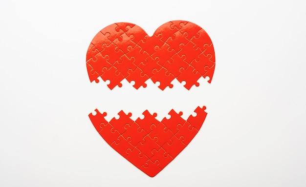 Bovenaanzicht van niet-verbonden delen van hartvormige puzzel op witte achtergrond