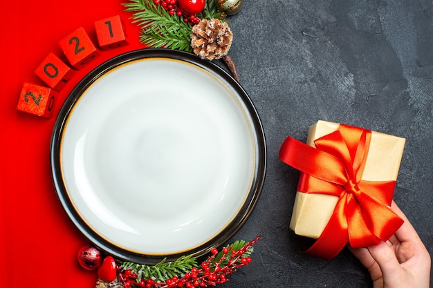 Bovenaanzicht van nieuwjaar achtergrond met bord en cadeau decoratie accessoires fir takken en cijfers op een rode servet op een zwarte tafel