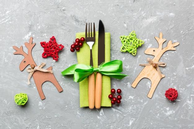 Bovenaanzicht van nieuwjaar gebruiksvoorwerpen op servet met vakantie decoraties en rendieren op cement,