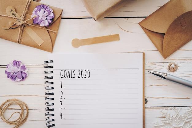 Bovenaanzicht van nieuwjaarsdoelen 2020 lijst lege notitieblok en kerstkaart op houten tafel met xmas decoratie.