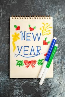 Bovenaanzicht van nieuwjaarsnota op grijs oppervlak