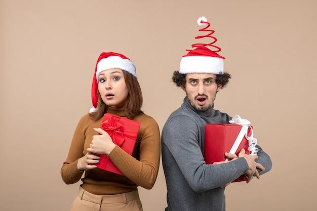 Bovenaanzicht van nieuwjaarsstemming en feestconcept - verrast mooi paar met geschenken die kerstman hoeden dragen