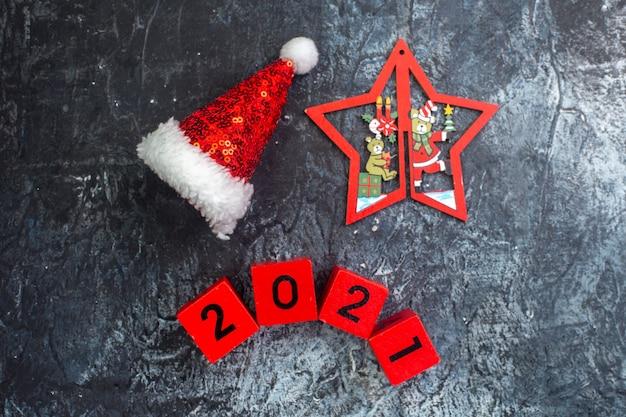 Bovenaanzicht van nieuwjaarsstemming met kerstmuts-nummers en ster met kersttekeningen op donkere ondergrond