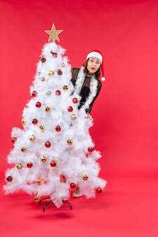 Bovenaanzicht van nieuwjaarsstemming met mooi meisje in een zwarte jurk met kerstman hoed