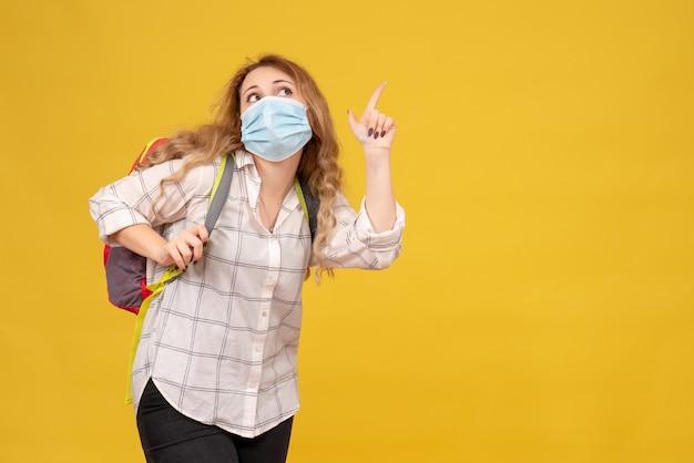 Bovenaanzicht van nieuwsgierig reizend meisje dat haar masker en rugzak draagt die op geel wijst